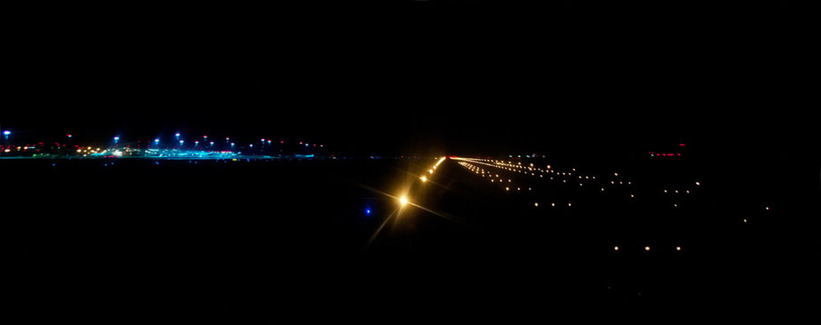 airport runway illuminated by bright landing lights at night