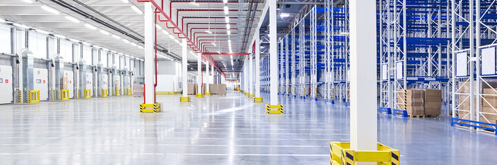 Empty huge distribution warehouse with high shelves and loading gates