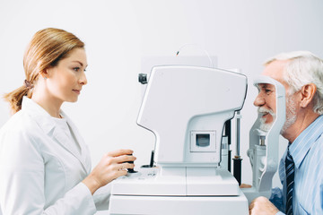 Doctor Optometrist examining old man's eyes with special eye equipment