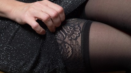 the woman in a small black dress adjusts the stocking on her leg.