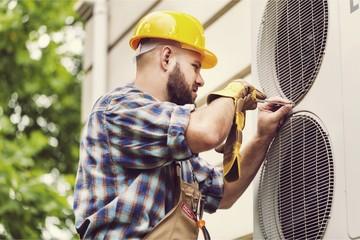 Man in hard hat installing air conditioner