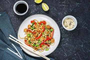 Stir fry noodles with vegetables and shrimps on dark stone background
