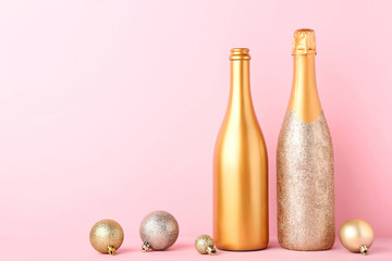Decorated champagne bottles with christmas baubles on pink background