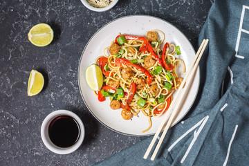 Stir fry noodles with vegetables and shrimps on dark stone background.