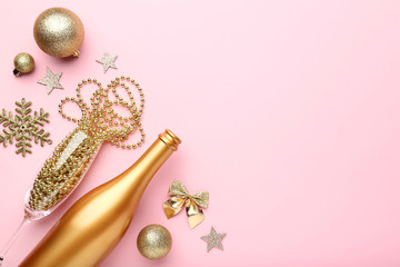 Champagne bottle with christmas decorations on pink background
