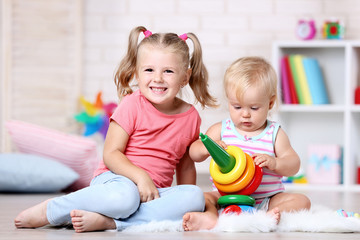 Little sisters playing with toys at home