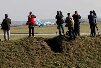 Journalists take pictures of a Ukrainian Su-27 fighter jet during the Clear Sky 2018 multinational military drills at Starokostiantyniv Air Base in Khmelnytskyi Region