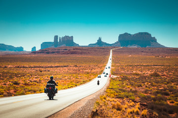 Zelfklevend Fotobehang Verenigde Staten Biker on Monument Valley road at sunset, USA
