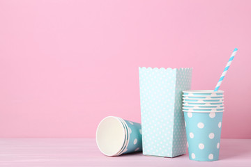 Blue paper cups with straws on pink background