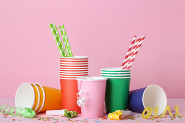 Colorful paper cups with straws and blowers on pink background