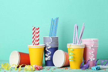 Colorful paper cups with straws and confetti on mint background