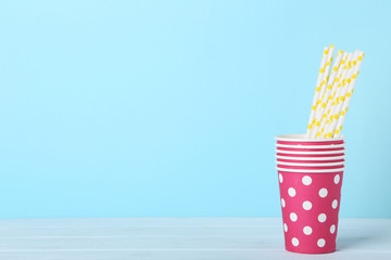 Pink paper cups with straws on blue background