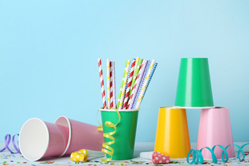 Colorful paper cups with straws with confetti on blue background
