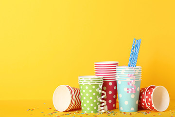 Colorful paper cups with straws and confetti on yellow background
