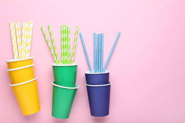 Colorful paper cups with straws on pink background