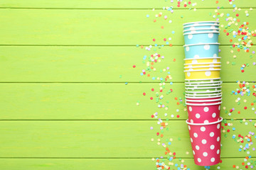 Colorful paper cups with confetti on green wooden table