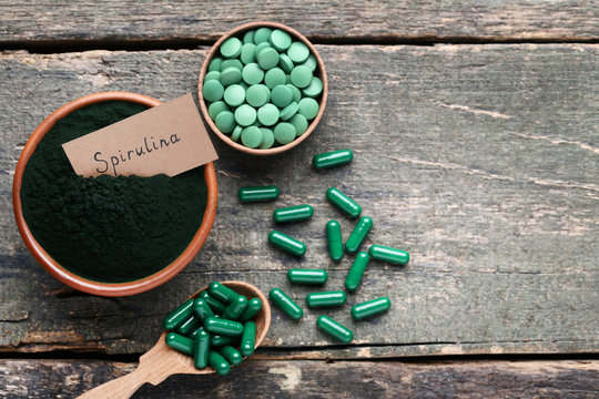 Spirulina powder and tablets on grey wooden table