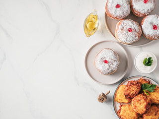 Jewish holiday Hanukkah concept and background. Hanukkah food doughnuts and potatoes pancakes latkes, oil and traditional spinnig dreidl. on marble table. Top view or flat lay. Copy space for text.