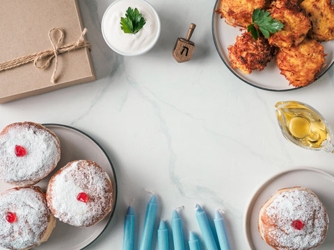 Jewish holiday Hanukkah concept and background. Hanukkah food doughnuts and potatoes pancakes latkes, oil, candles, gift box and traditional spinnig dreidl. Top view or flat lay. Copy space for text