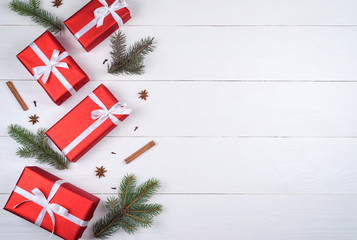 Christmas background with red gift boxes, fir tree branches, cinnamon sticks and star anise, free space. Red Christmas gift boxes on white wooden background, copy space. Flat lay, top view