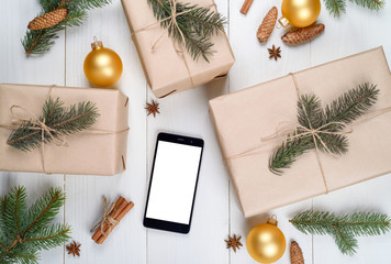 Christmas background with mobile phone with blank white screen, gifts, fir branches, cones, cinnamon on wooden background, copy space. Flat lay, top view. Christmas application mock up template
