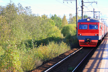 Vintage Red Train Arriving at Outdoor Platform on Railway Station. Summer Day View of Old Train on Railroad Track with No People and Forest Trees on Background