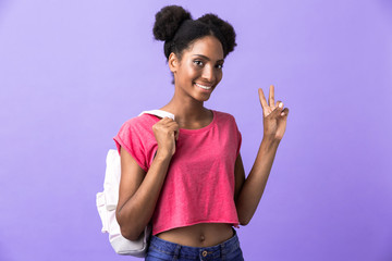 Photo of brunette african american woman student wearing backpack showing peace sign, isolated over violet background
