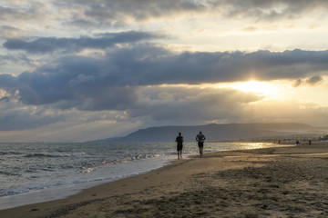 couple running on the beach at sunrise
