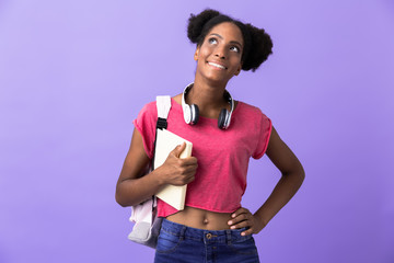 Photo of african american female student wearing backpack holding exercise book, isolated over violet background