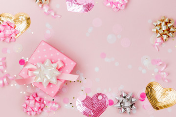 Confetti, bows and paper decorations. Valentines day or birthday party concept theme. Flat lay, top view.