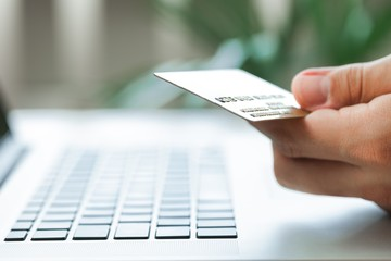 Closeup of a Man Typing on a Laptop and Holding a Credit Card