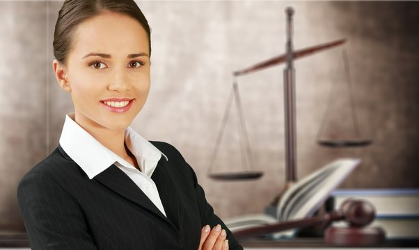Scales of justice and businesswoman sitting at