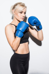 Beautiful smiling young fitness woman wears blue boxing gloves over grey background