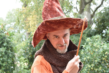 Quirky contemporary wizard wearing a hat and  holding a lighted-up magic wand.