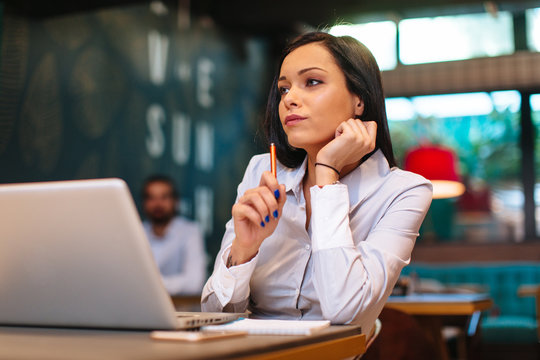 Young business woman thinking and takes notes in cafe