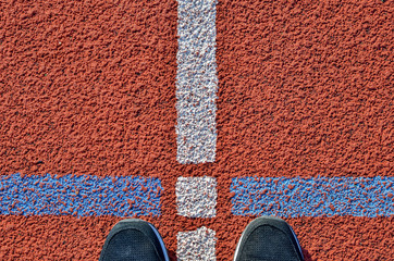Feet in sneakers standing in front of the tracking field line. Top view