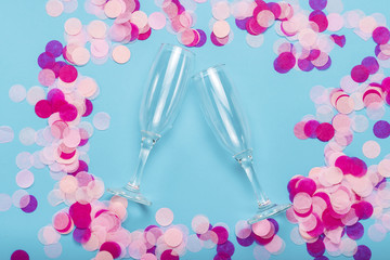 Pink confetti and empty portions for champagne on a blue background. Party and holiday concept. Flat lay, top view