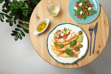 Flat lay composition with melon and prosciutto appetizer served on wooden table