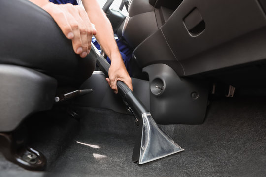 Man cleaning automobile salon with vacuum cleaner, closeup. Car wash service