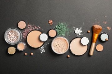 Flat lay composition with various makeup face powders on dark background