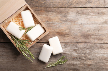Flat lay composition with soap bars, rosemary and space for text on wooden background
