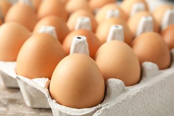 Raw chicken eggs in carton, closeup view