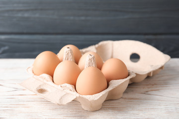 Carton of raw chicken eggs on wooden table against gray background