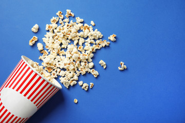 Paper cup and tasty popcorn on color background, top view with space for text. Cinema snack