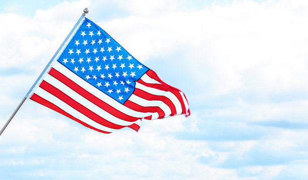 American flag near river on cloudy day. Space for text