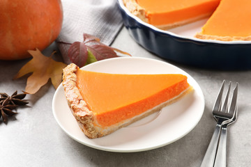 Plate with piece of fresh delicious homemade pumpkin pie on gray table