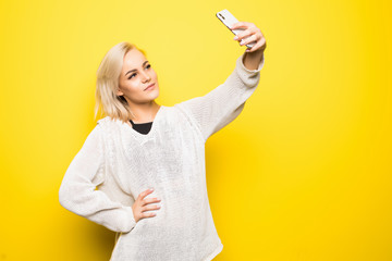 Portrait of cool cheerful girl having video-call with lover holding smart phone in hand shooting selfie on front camera isolated on yellow background e