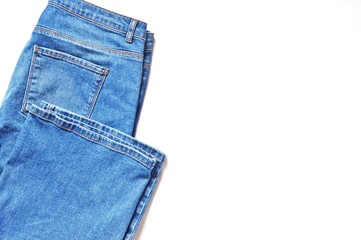 Blue jeans on a white background. Flat lay photo, copy space