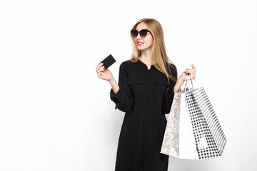 successful girl in black dress and with red lips holding bags, for shopping and credit card on white background, black Friday, shopping,