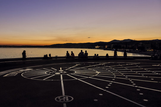 Sundial in Nice, France at sunset on Promenade des Anglais with outline of people. A famous place in French Riviera.